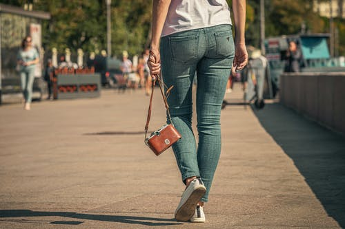 Woman in White Tank Top and Blue Denim Jeans With Red Sling Bag Walking on Street