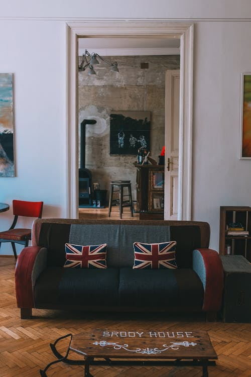 Interior of stylish living room with comfortable couch decorated with United Kingdom flag cushions and wooden furniture and floor