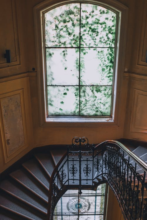 Staircase near window with muntin in old classic house