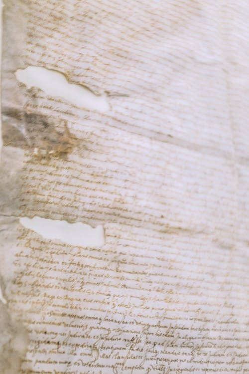 Old shabby handwritten manuscript on dirty torn paper sheet with crumples and cracks