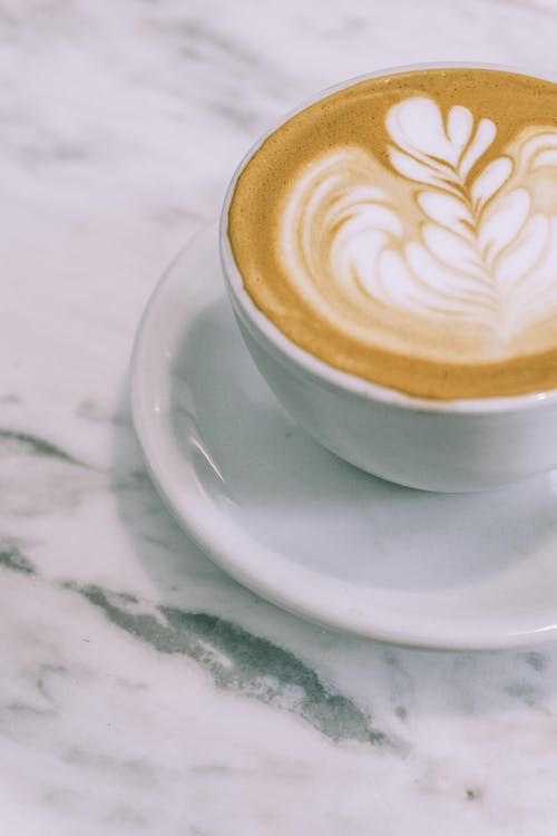 Cup of aromatic cappuccino served on marble table