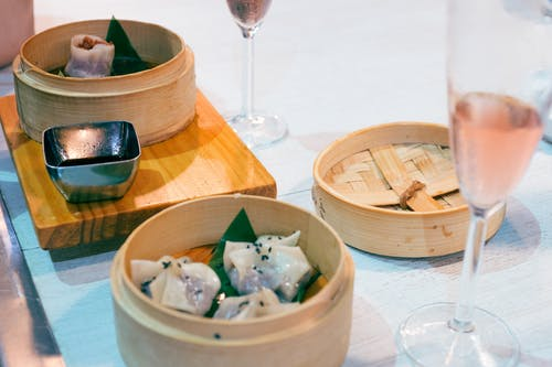Delicious traditional Asian dim sum dishes in wooden bowls served on table