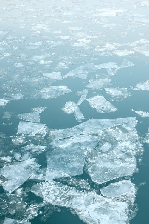 Large ice pieces floating in ocean water