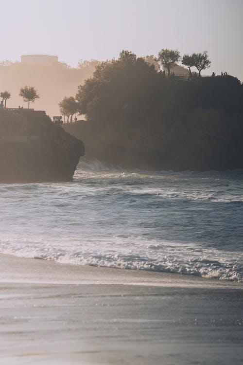 霧の中の山の近くの砂浜の海のビーチ