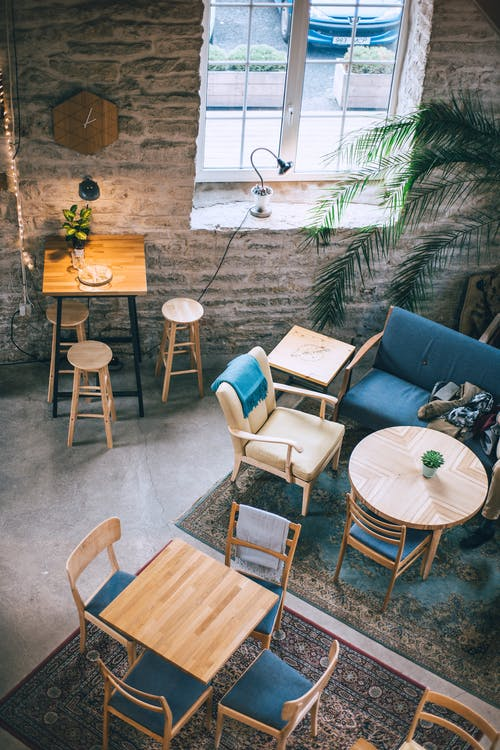 From above of cafeteria interior with wooden tables and chairs on rugs near rough stone wall in daytime