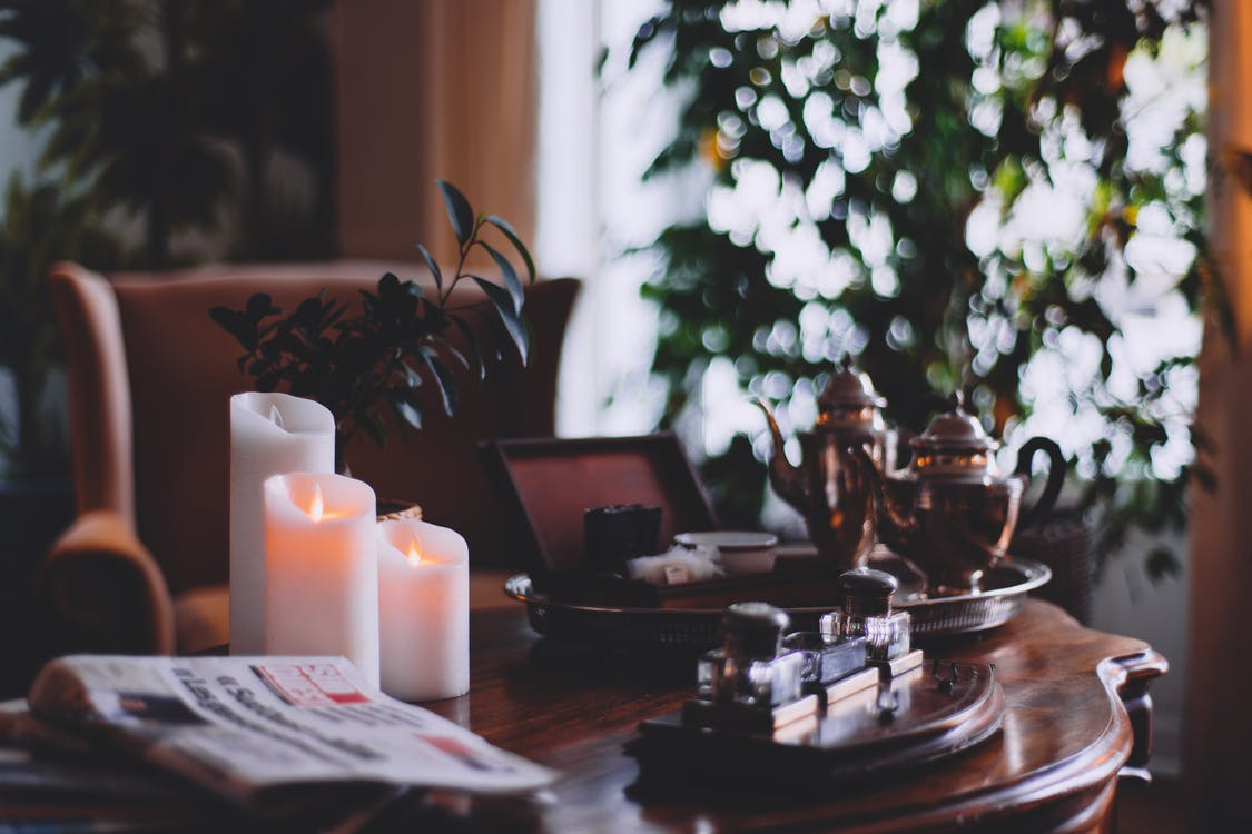 Flaming wax candles near metal teapots on tray and cozy armchair in house room
