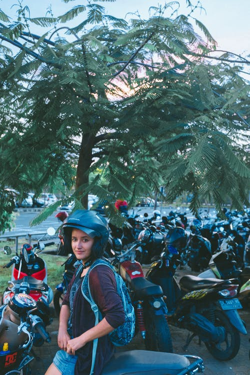 Teen in protective helmet resting on motorbike