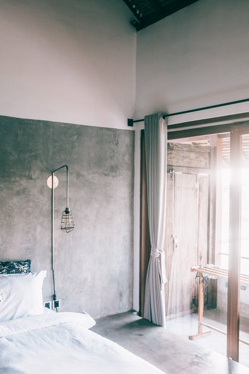 Bedroom interior with cement walls in sunlight