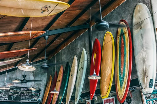 Assorted old bright surfboards with shabby surface near hanging lamps from wooden ceiling in daytime