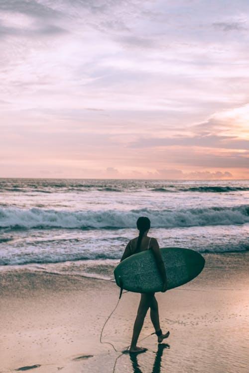有衝浪板的女性衝浪者在揮動的海附近的海灘上走