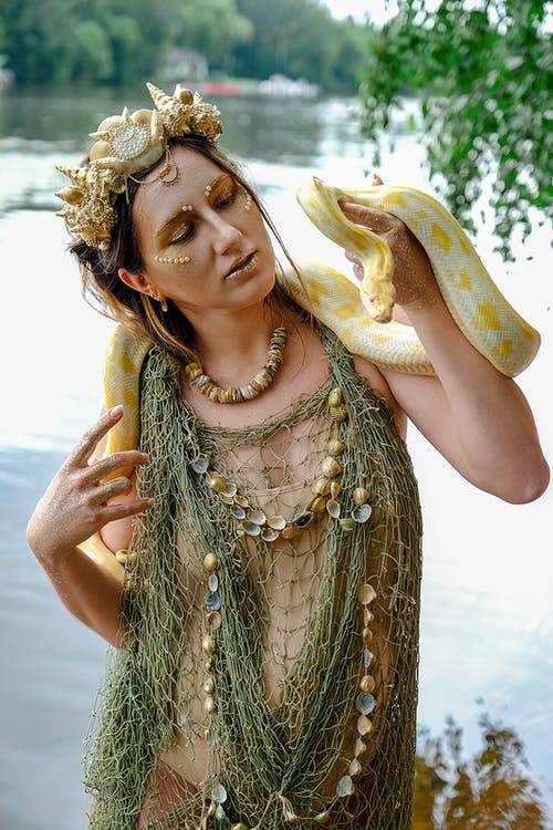 Fashionable young pregnant woman with reticulated python on shoulders