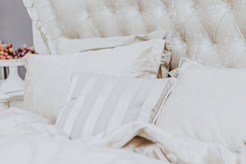 Soft comfortable bed with white pillows blanket and headboard in cozy bedroom in morning