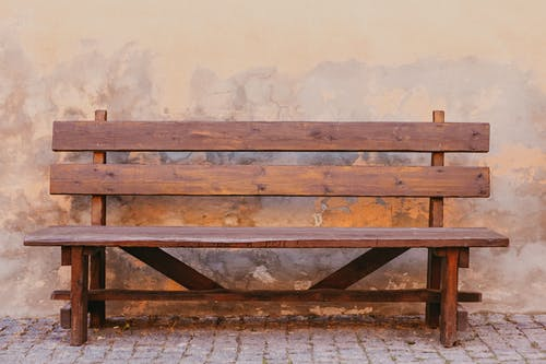 Aged wooden bench placed on paved ground against shabby dirty weathered stone wall of building