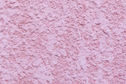 Pink painted background of textured wall