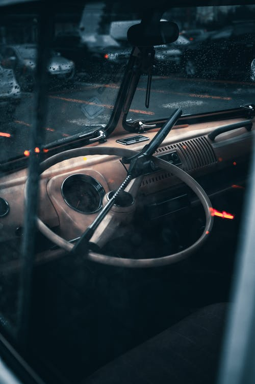 Old simple round black steering wheel in cabin of old vintage automobile on pavement on parking