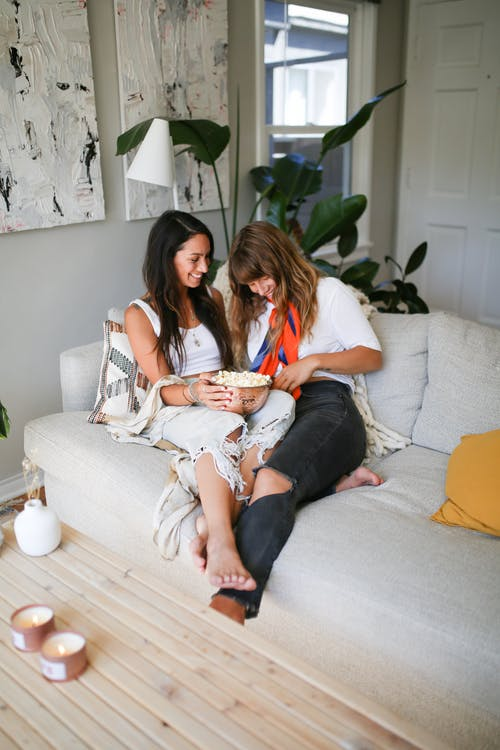 2 Women Sitting on White Couch