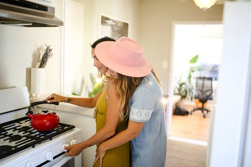 Woman in Blue Denim Vest and Brown Hat Standing in Front of Stove