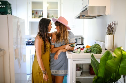 Woman in Yellow Tank Top and Blue Denim Shorts Wearing Red Hat Standing in Kitchen