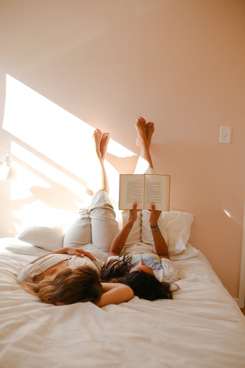 Woman in White Shirt Lying on Bed Reading Book