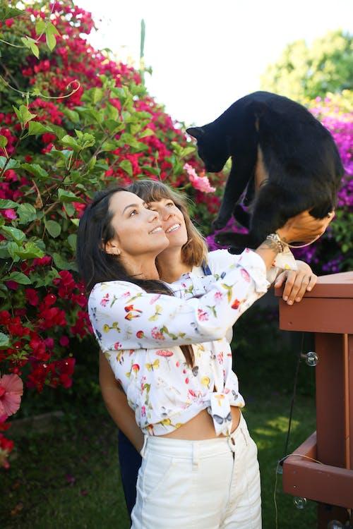 Girl in White and Red Floral Dress Hugging Black Short Coated Dog