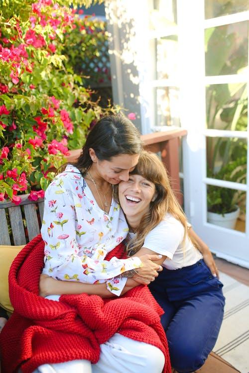Frau Im Weißen Und Rosa Blumen Langarmhemd, Das Auf Rotem Stuhl Sitzt