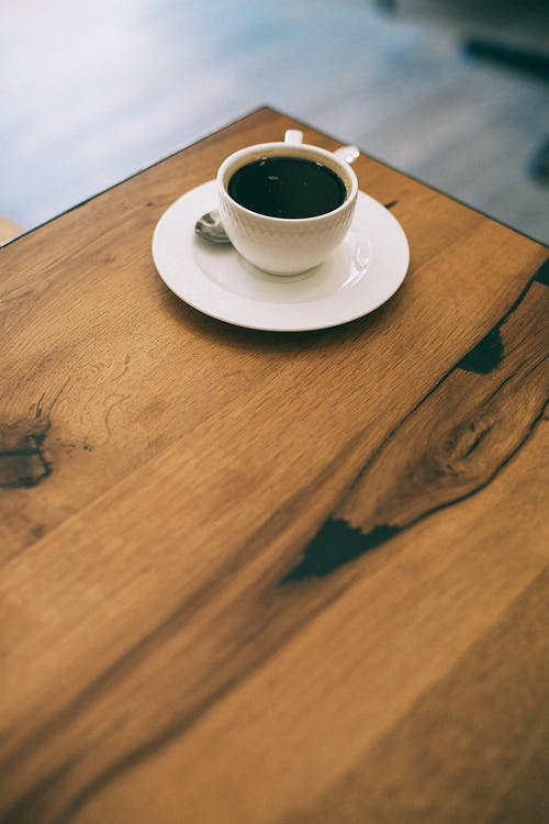 Cup of coffee on wooden table in cafe