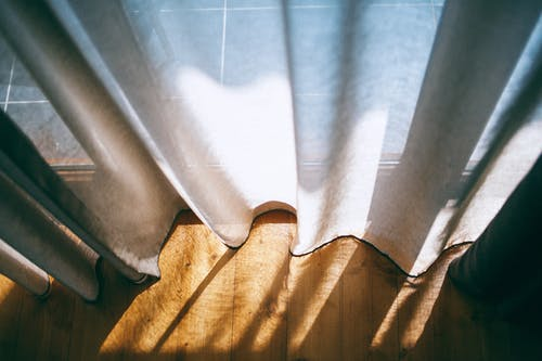 From above of panoramic window with transparent curtains lightened by sunshine in room