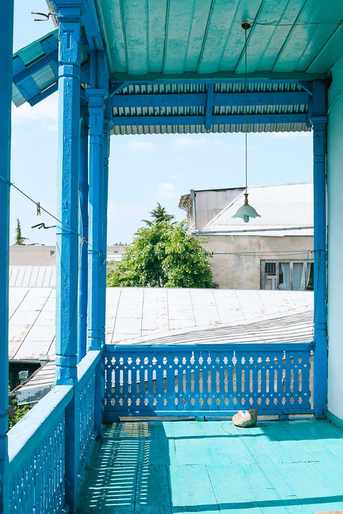 Timber terrace with blue fence of rustic house in sunny settlement with residential buildings