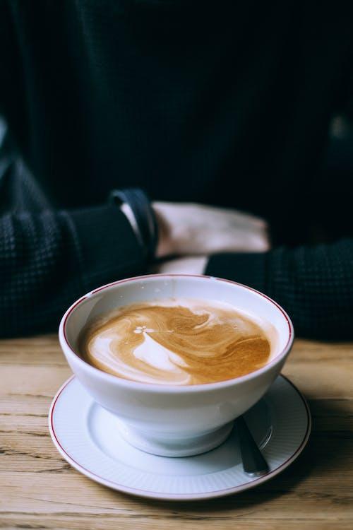 Man having coffee in cafe in ceramic mug