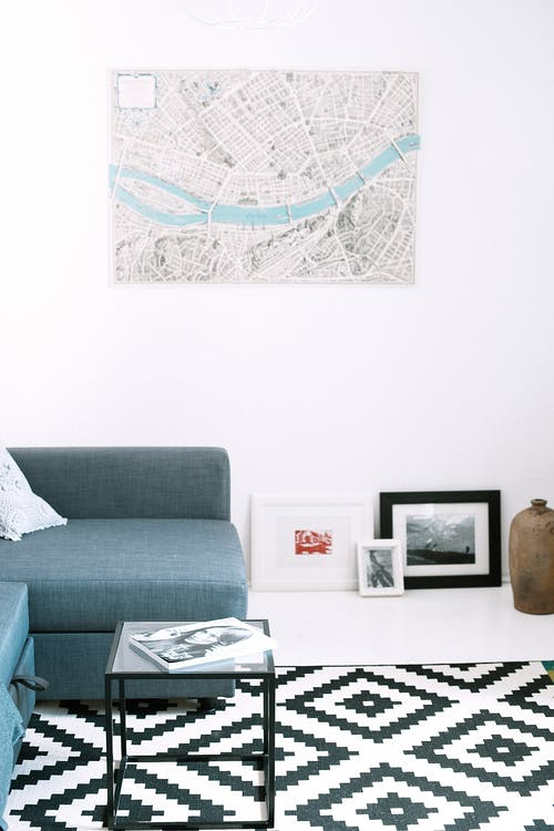 Comfortable couch placed on tiled floor near paintings against white wall with city map poster in spacious light living room