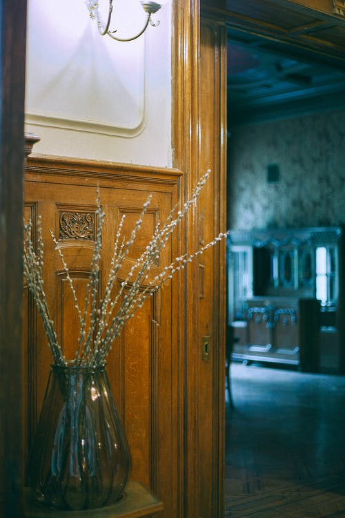Glass vase with dry plant placed near wooden doorway near entrance in room with vintage interior and old fashioned design in apartment