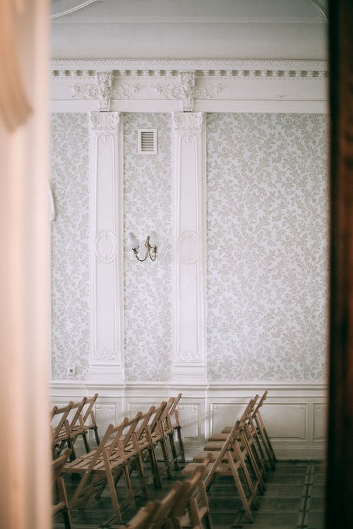 View through doorway of wooden chairs placed in row on tiled floor in room with ornamental wall with white columns