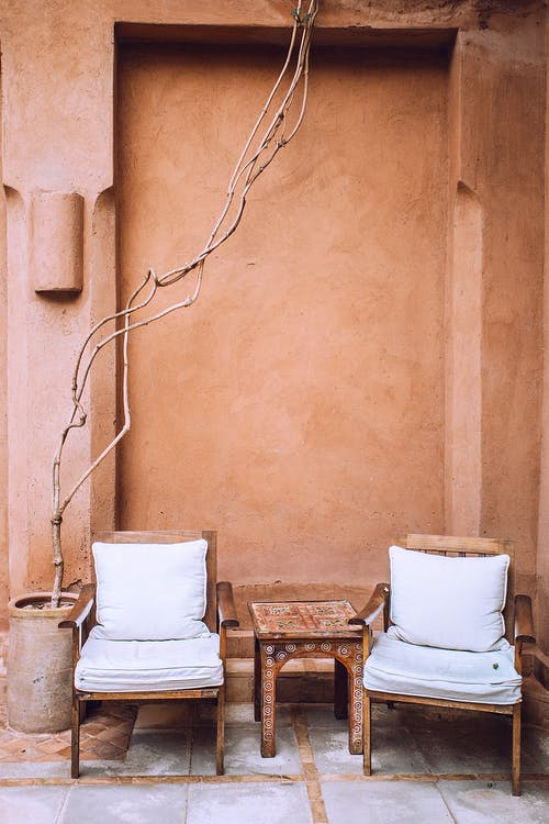 Aged armchairs near small table in patio