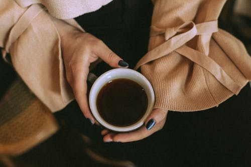 From above of crop anonymous female in soft apparel with manicure holding mug of black coffee