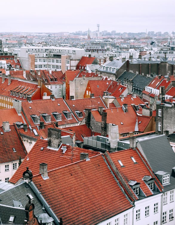 From above of aged dwelling building facades with attic windows on bright roofs in city