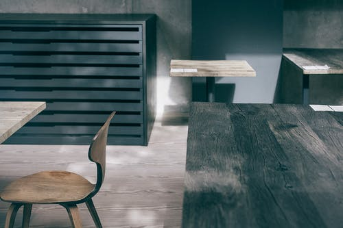 Wooden tables of different sizes near chair and ribbed cabinet on floor in house in sunlight