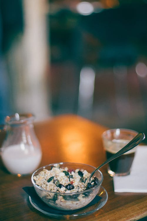 From above of bowl with oatmeal and fresh grapes near glass of black coffee and jug of milk