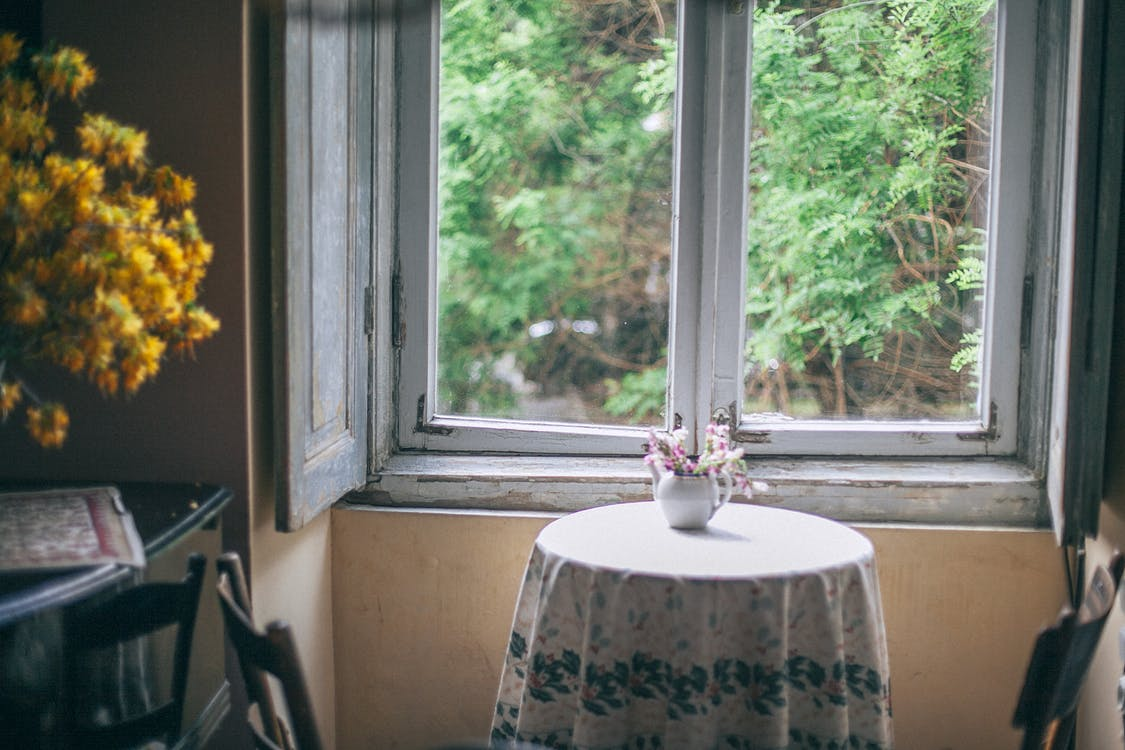 Blooming flowers in vase on table in old house