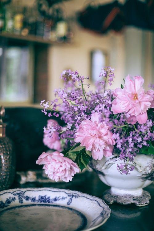 테이블에 장식 접시 근처 꽃병에 밝은 분홍색 모란