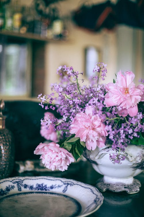 Bright pink peonies in vase near ornamental plate on table