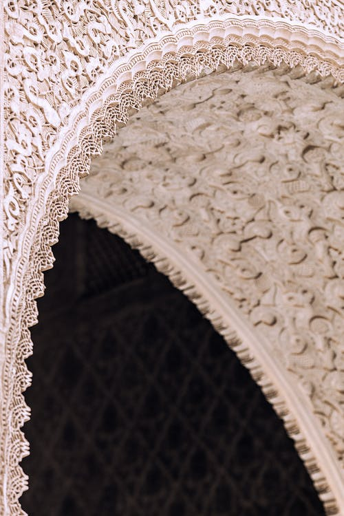 From below of aged stone building with decorative arch in form of lace in city