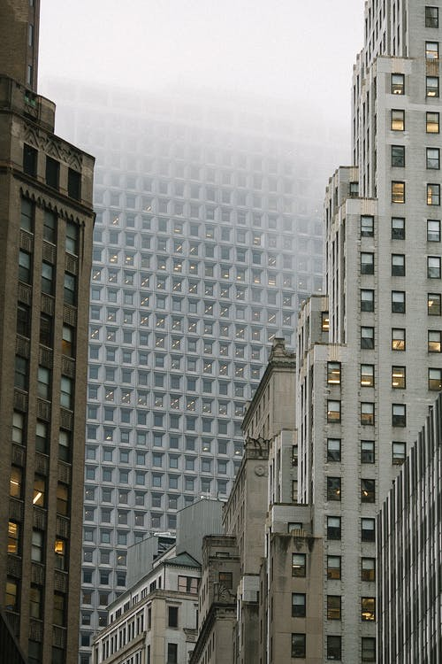 Low angle of modern multistage building exteriors with geometric windows on front walls in misty weather in town