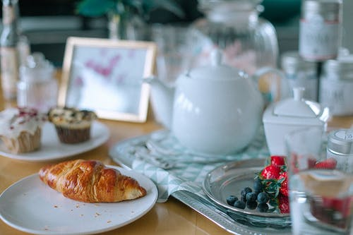 Appetizing croissant and muffins served on table with teapot and berries