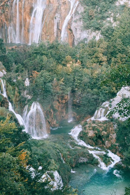 From above picturesque view of rapid waterfalls with foamy streams on ridge with green trees in summer