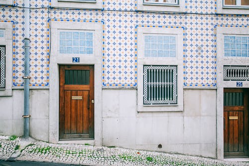 Facade of modern residential building with wooden doors and ornamental tiled walls in daylight