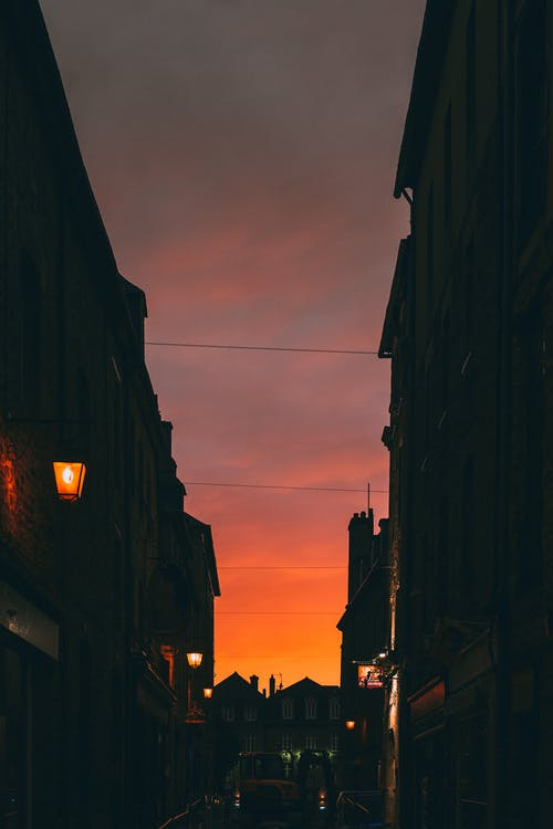 Narrow town street with residential house silhouettes and lanterns beneath majestic dark red sunset sky