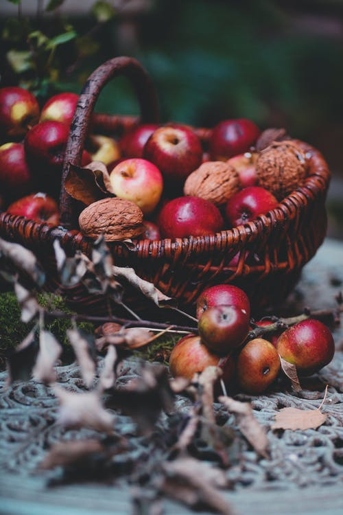 Still life composition of sweet red apples and walnuts heaped in wicker basket on garden table in daylight