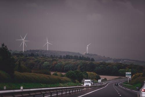Asphalt highway running through grassy lush valley with modern wind turbine generators under gloomy overcast sky