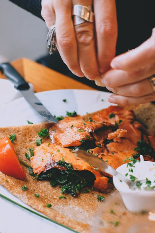 Crop faceless woman garnishing salmon steak with herbs