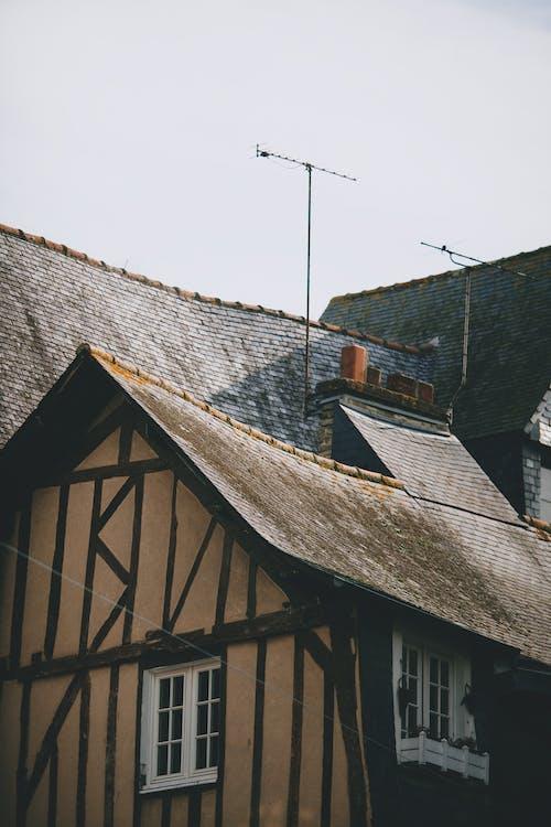Aged residential house exteriors under light sky